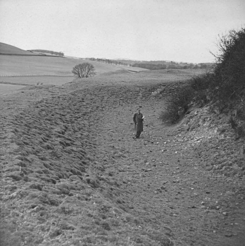 Copy of view of a man (R.J.C. Atkinson?) standing in the ditch of the Mote of Urr.