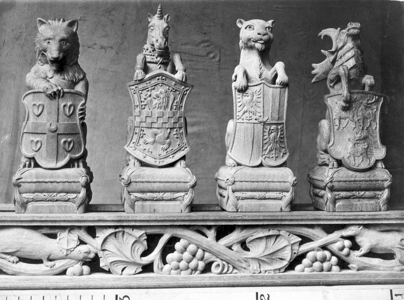 Photographic view of bear/wolf, unicorn, tiger/panther/lion and stag oak staircase finials, each holding a shield. Scanned image of E 23145.
