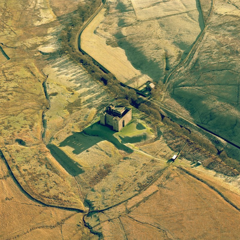 Hermitage Castle, oblique aerial view centred on the remains of a castle and earthwork castle, taken from the North West.