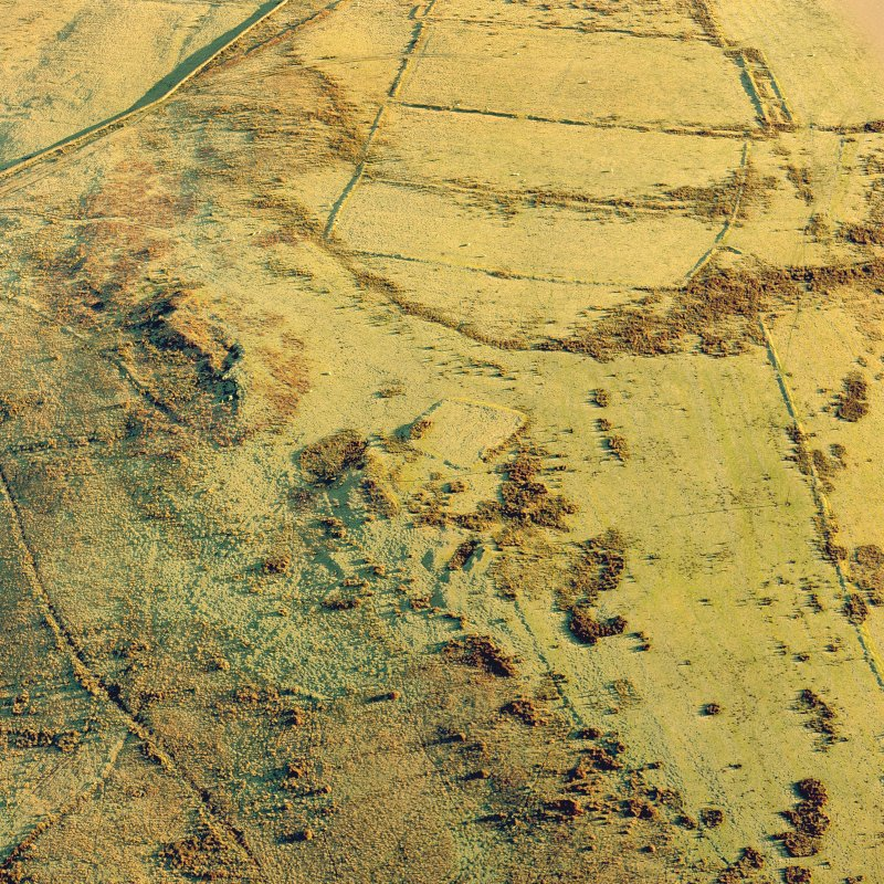Oblique aerial view of Toft Knowes centred on the remains of a farmstead and quarries with the remains of a field-system, rig and pens adjacent, taken from the W. Digital image of D/24579/CN.