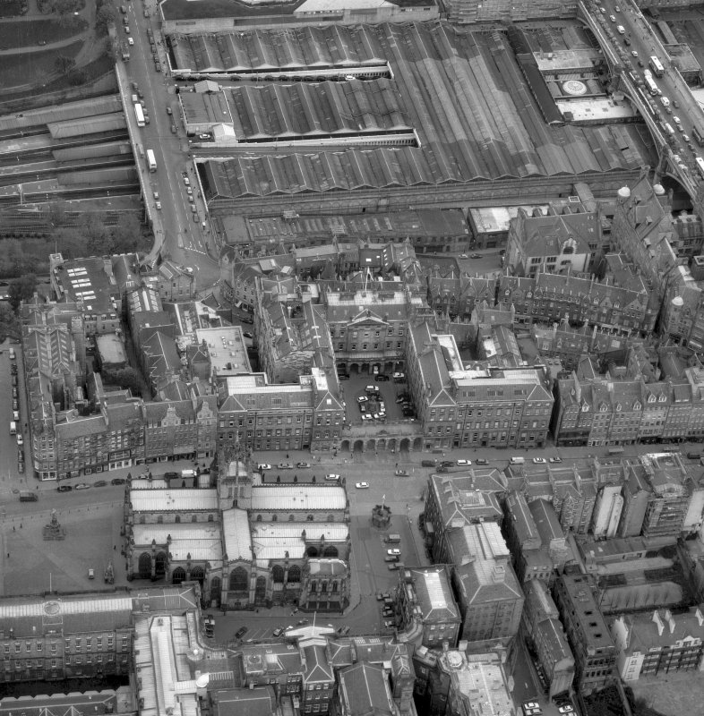 Oblique aerial view showing High Street between North Bridge and Lawnmarket, with St Giles' Cathedral in foreground, City Chambers in centre and Waverley Station at top.