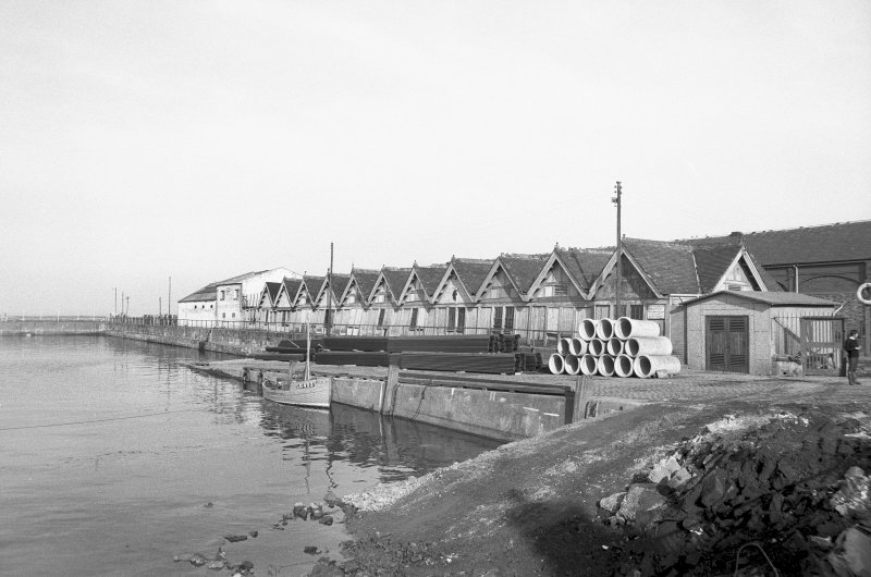 View from SW showing E side of pier with jetty and wooden sheds