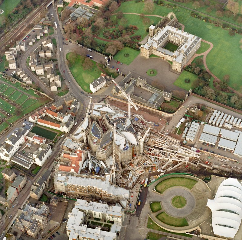 Oblique aerial view centred on the construction of the Scottish Parliament with exhibition centre and palace adjacent, taken from the SW.