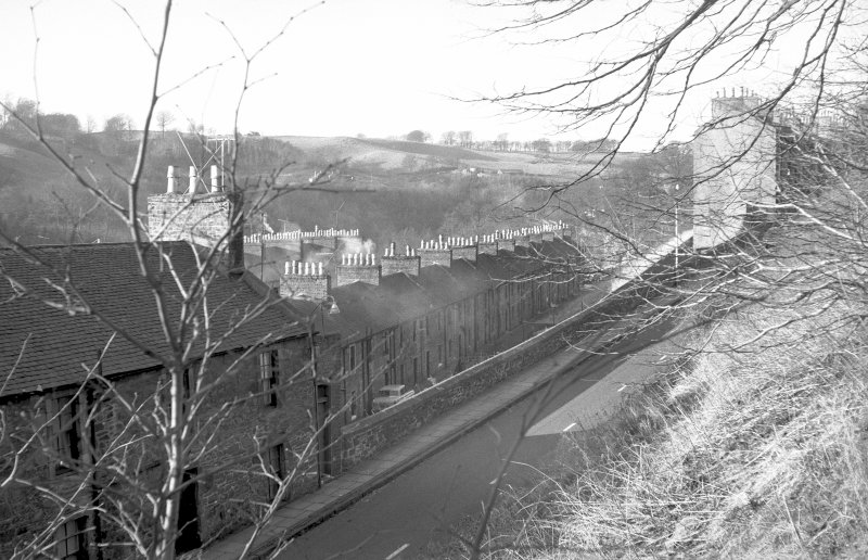 View from E showing NE front of no 128 New Lanark Road with Long Row in middle background and no 158 New Lanark Road in right background