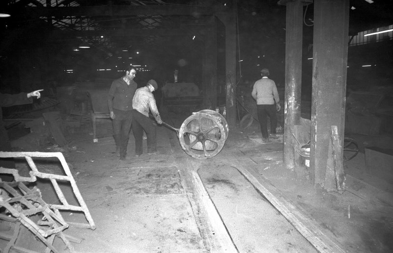 Interior View showing men working iron ladle