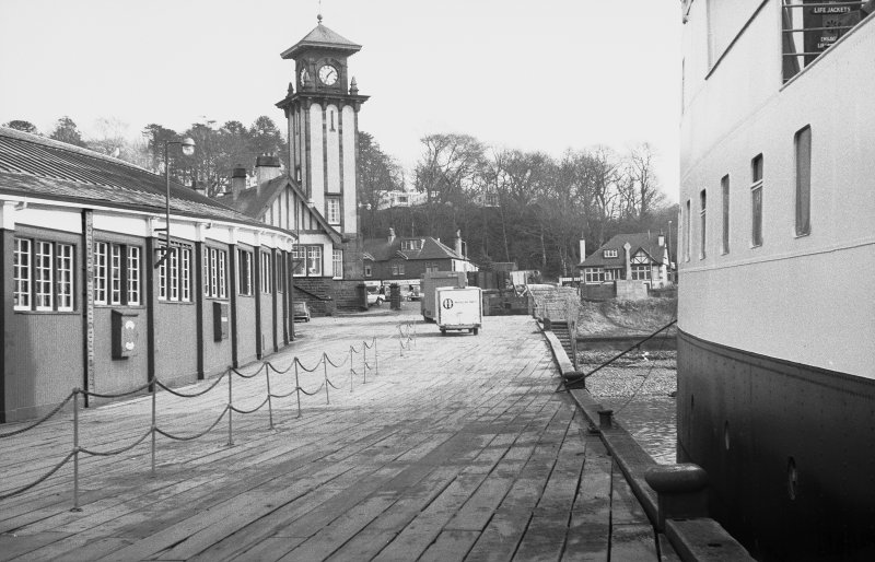 General view from W showing covered walk-way, clock-tower and pier