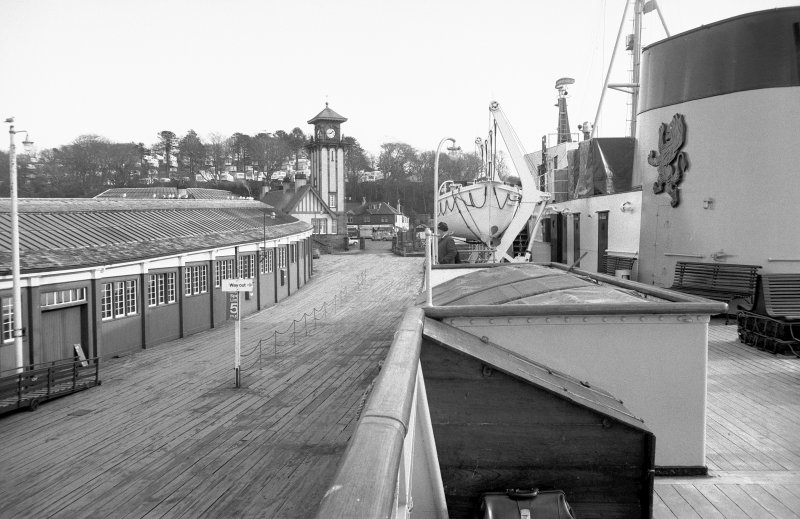 General view from W on MV Glen Sannox showing covered walk-way and pier with clock-tower in background