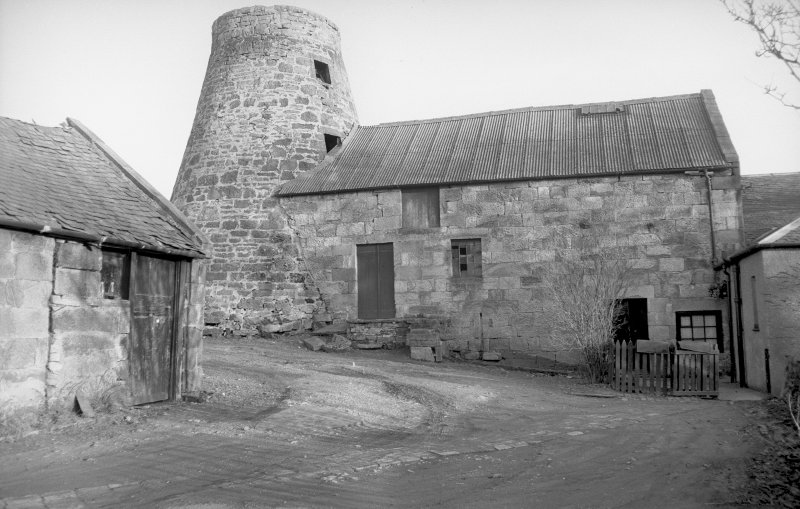 View from W showing tower and WNW front of mill block with part of ancillary building in foreground