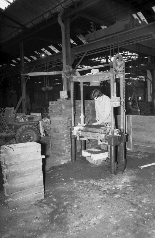 Interior View showing man working on hand-moulding machine