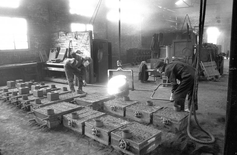 Interior View showing men pouring iron into mould