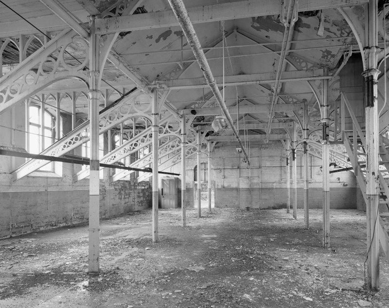 Interior. View of cast-iron roof trusses and columns with gothic shaped wooden infills central section on top floor of main building. Digital image of A 38494