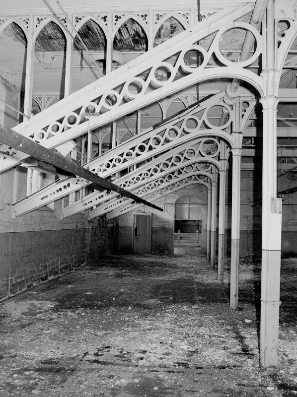 Interior. View of cast-iron roof trusses and columns with gothic shaped wooden infills in central section of top floor of main building. Digital image of A 38495
