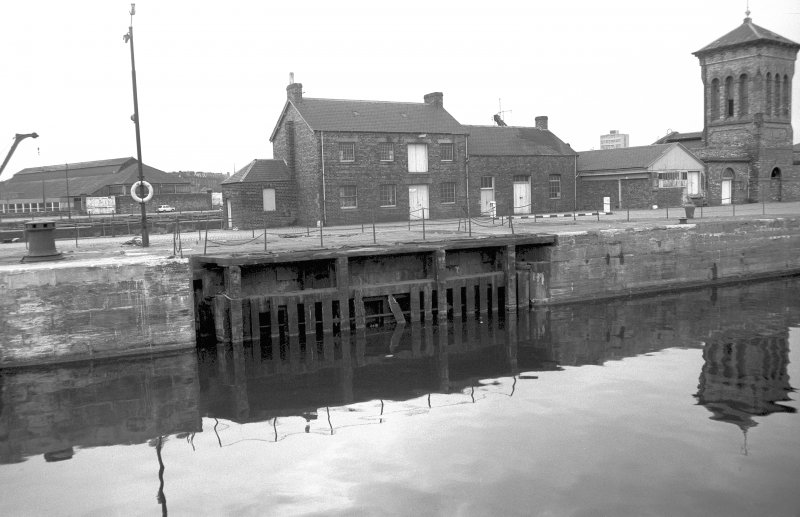 View from NNE showing S lock gate at entrance to Albert Dock with workshops and part of pumping station in background