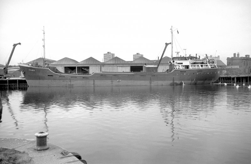 View from ENE showing coaster MV Fylhix moored on wharf opposite dry dock entrance