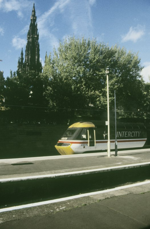 View from S showing Edinburgh - Aberdeen train at platform with Scott Monument in background