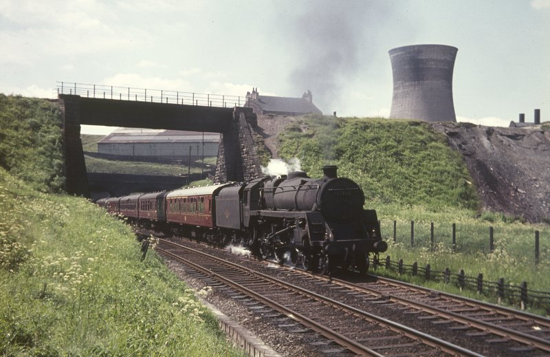View from NNE showing Glasgow - Aberdeen train passing below Pinkston Road with power station cooling tower in background