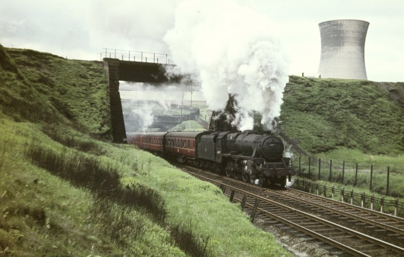 View from NNE showing Glasgow - Aberdeen train passing below Pinkston Road on the Cowlairs Incline with power station cooling tower in background.