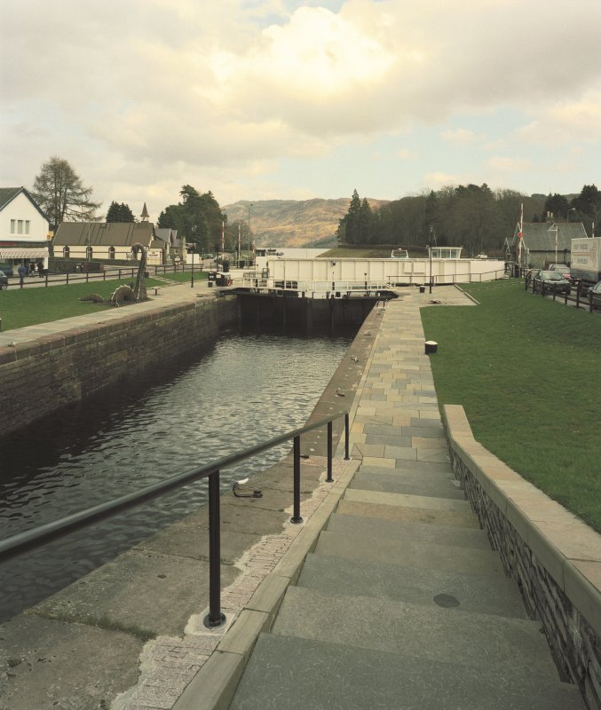 Fort Augustus, Swing Bridge over Caledonian Canal An elevated distant view looking east-north-east down towards the swing bridge, with the first pair of lock gates visible immediately before the bridge. Digital image of D 64040 CN