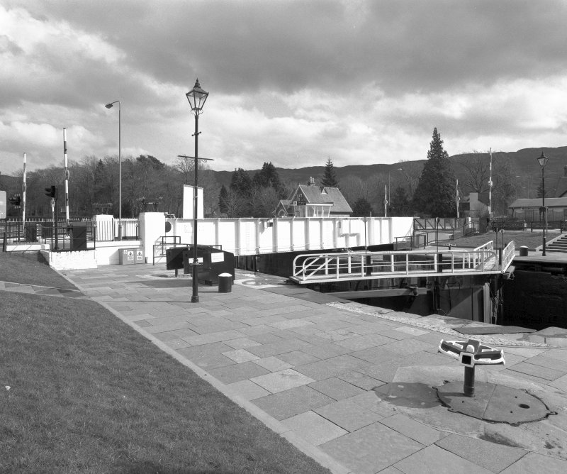 Fort Augustus, Swing Bridge over Caledonian Canal An oblique view of the swing bridge, looking east, with a pair of lock gates in the middle distance.  In the foreground stands a capstan Digital image of D 64043