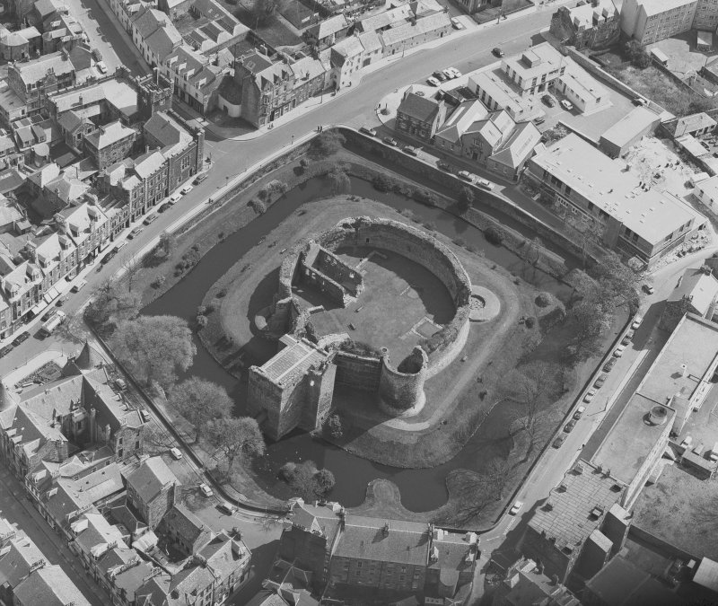 Oblique aerial view centred on the remains of Rothesay Castle, Bute.