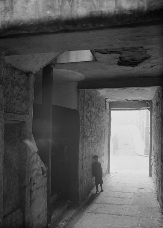 General view in Borthwick's Close, Edinburgh, with small boy leaning on wall.