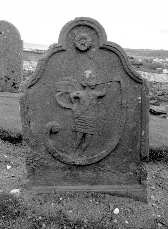 General view of gravestone commemorating John King, 1764 in the churchyard of Boyndie Old Parish Church. Rosette and angel with trumpet with scroll emerging.