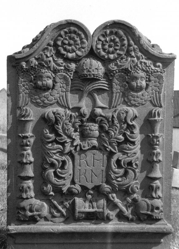 Errol Old Parish Churches, Errol Churchyard. General view of gravestone of Margaret Hill, 1754. Rosettes, crown over crossed palm fronds and vine, double winged souls and pair of double torches. Foliate crest Insc: 'R.H K.M'. Emblems of mortality linked by ribband. (skulls, arrows of Death, hourglass and crossed bones). Digital image of A 37033 PO
