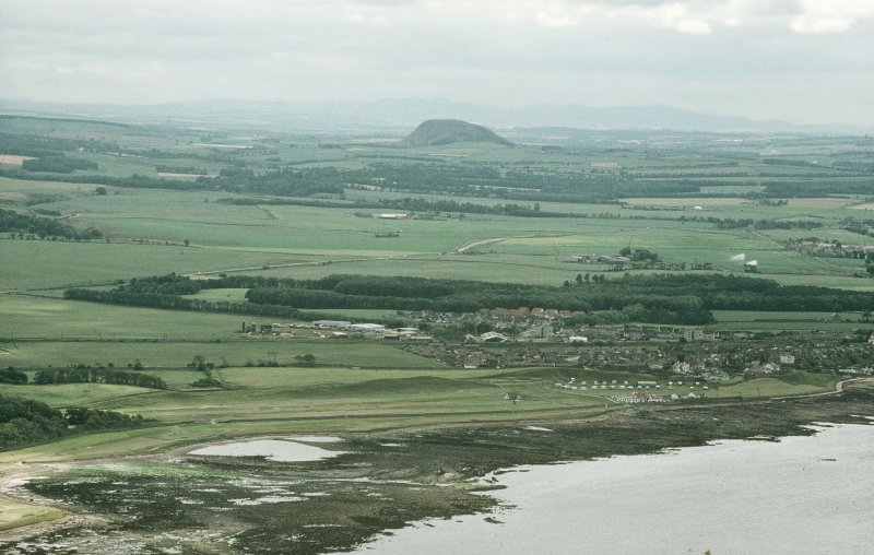 Oblique aerial view, taken from the NE, looking SW from the sea and across the town of Dunbar (NT67NE 96), with Traprain Law fort (NT57SE 1) in the distance.