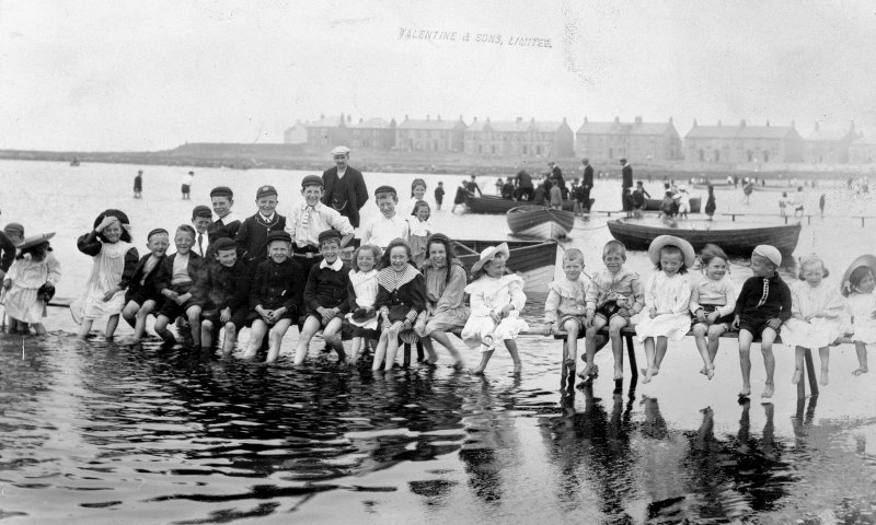 Historic photograph showing general view of school outing at beach.