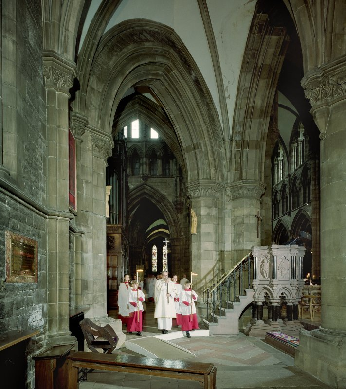 Interior. View of aisle showing crucifix bearer at head of choiristers' procession passing by pulpit.
