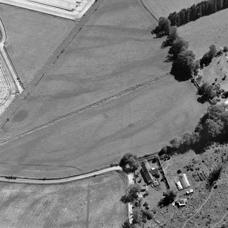 Tullichettle, oblique aerial view, taken from the NNW, centred on the cropmarks of an old road, and a pit-defined cursus monument.