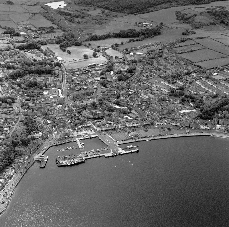 Oblique aerial view of Rothesay, taken from the N, centred on the town.  A harbour is visible in the bottom half of the photograph.  Rothesay castle and Winter Gardens are visible in the centre of the photograph.