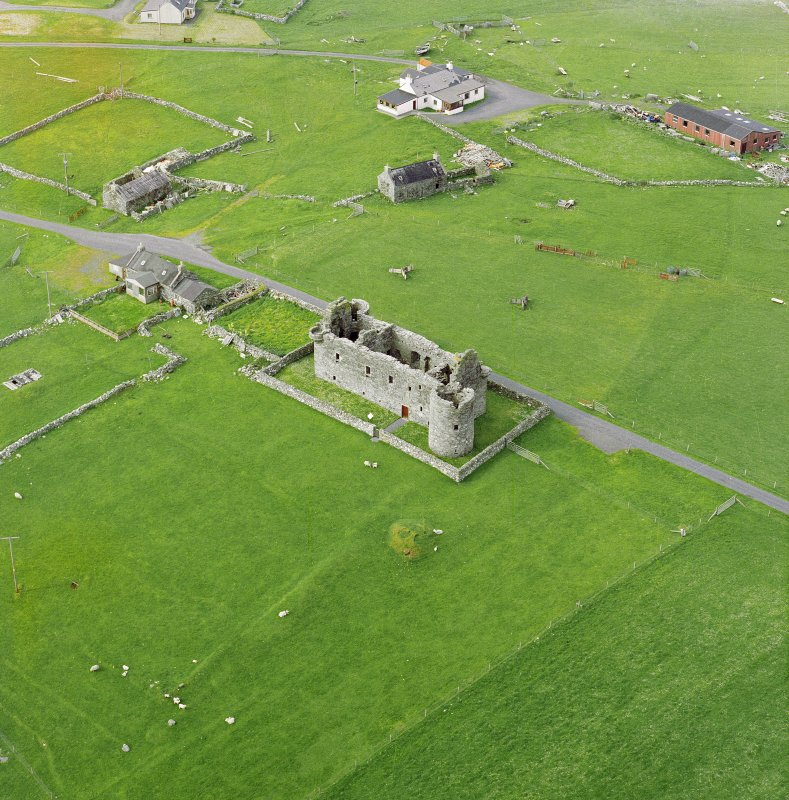 Oblique aerial view centred on the remains of Muness Castle with a mound adjacent, taken from the South.