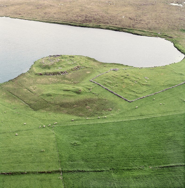 Oblique aerial view centred on the remains of the broch with the remains of the buildings and burnt mound adjacent, taken from the ENE.