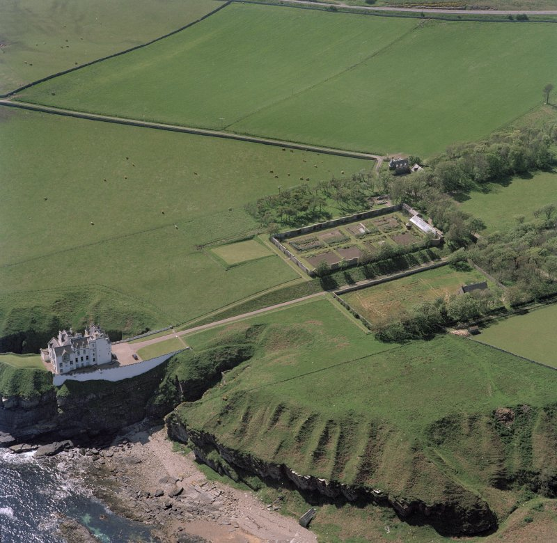 Oblique aerial view of Dunbeath Castle and walled gardens from NE.