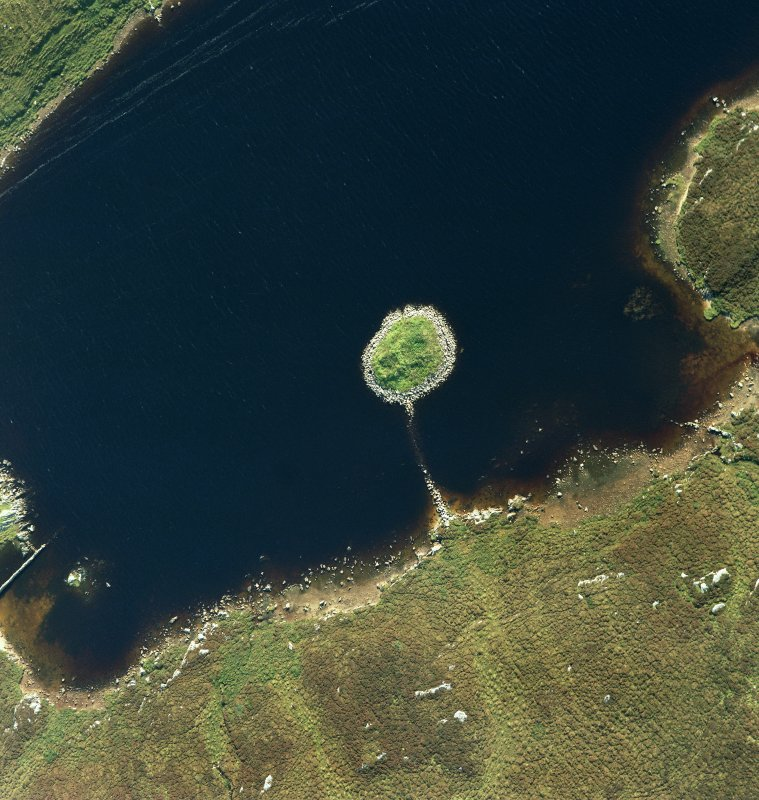Oblique aerial view of Loch nan Cinneachan centred on the remains of an island dwelling on a crannog, taken from the SE.