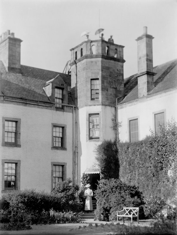 View of re-entrant angle of Innergellie house with well dressed lady on stair and ladies posing with parasols on the parapet.