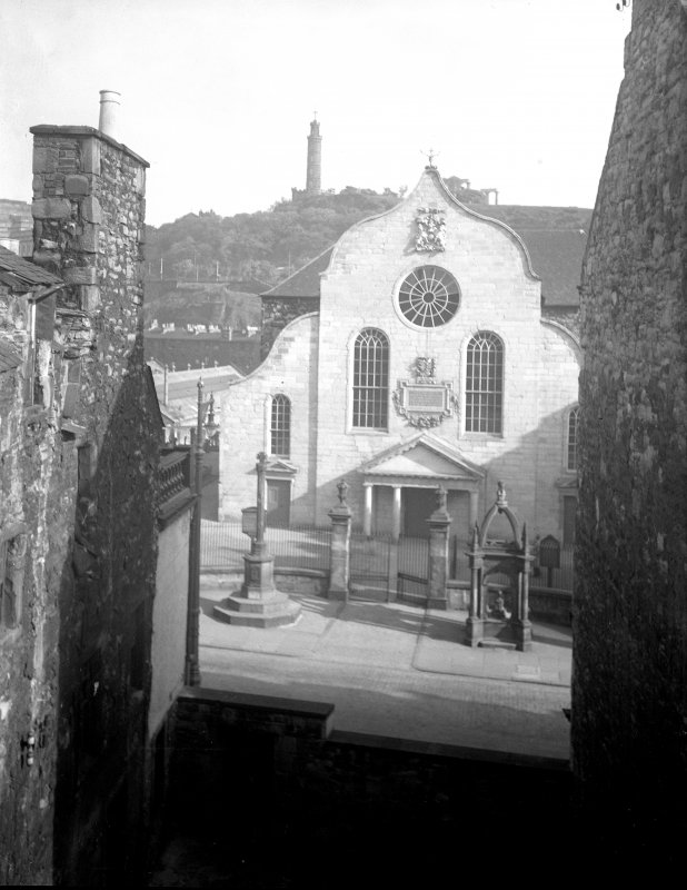 Elevated view of Canongate Church, Edinburgh, from south, with Burgh Cross and Home Fountain in front, and Nelson's Monument and National Monument behind.