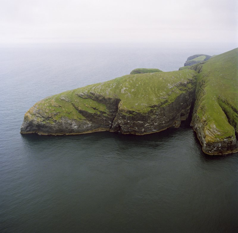 General oblique aerial view centred on the remains of the promontory fort, with coastal promontories and sea stacks adjacent, taken from the S.