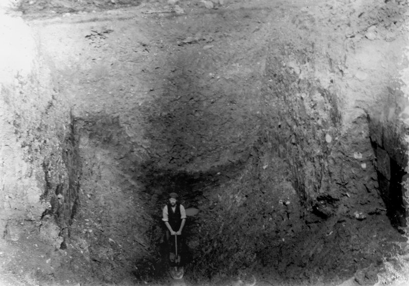 Excavation photograph showing workman indicating scale in excavated trench, taken during the James Curle excavation 1905-1909.