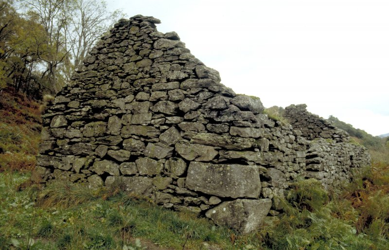 SW gable of building (BL00 733) within township. There are cupmarks on the two lower quoins in the S corner (in foreground).