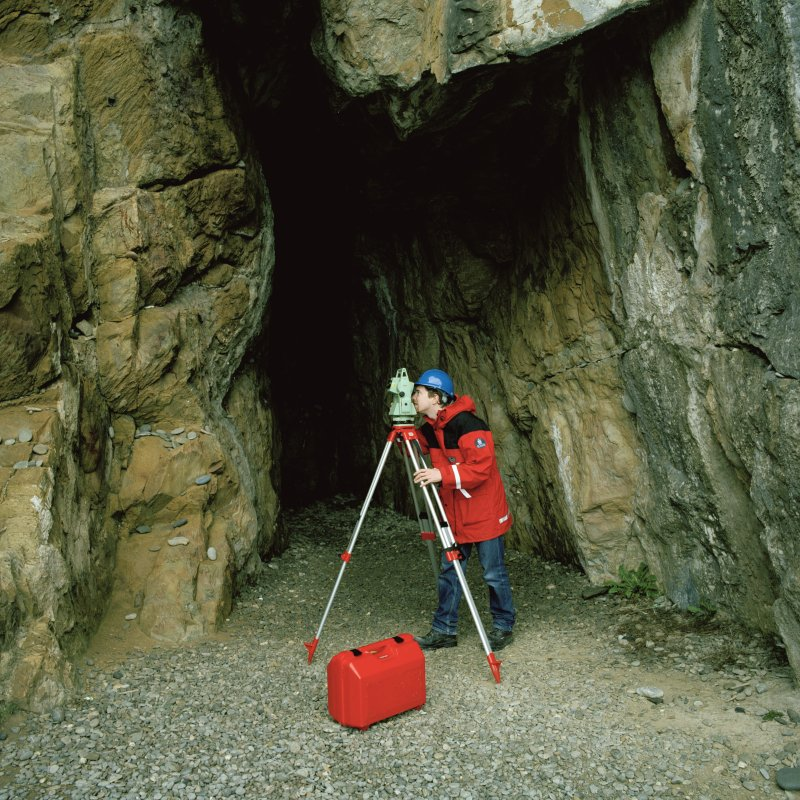 RCAHMS AT WORK. Cave entrance being surveyed by James Hepher, Survey and Graphics, using EDM.