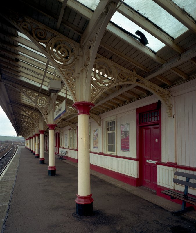 Detailed view from WSW along south-bound platform, showing ornate cast-iron columns and trusses supporting awning, and wooden facade of extended station buildings