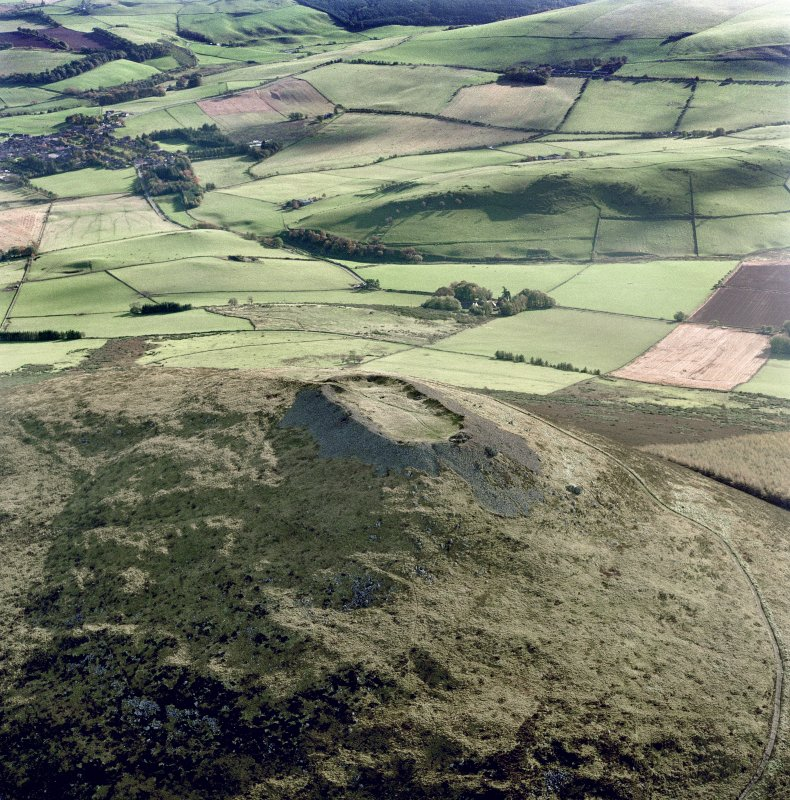 Scanned image of oblique aerial view of Tap o' Noth centred on the remains of the fort, taken from the W.