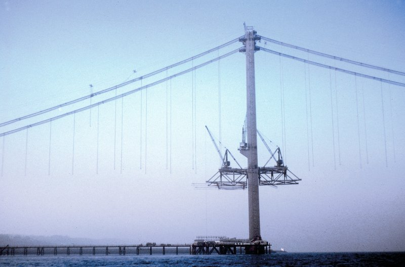 View west of South Main Tower with deck erection cranes assembled on first panels of suspended structure on each face of tower. Copy of original 35mm colour transparency Survey of Private Collection