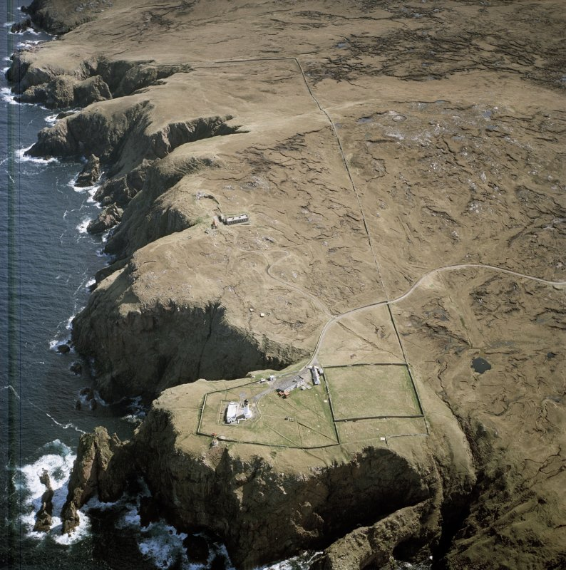Oblique aerial view centred on Cape Wrath lighthouse, keepers' cottages, cottages and support buildings with the radar station adjacent, taken from the NW.