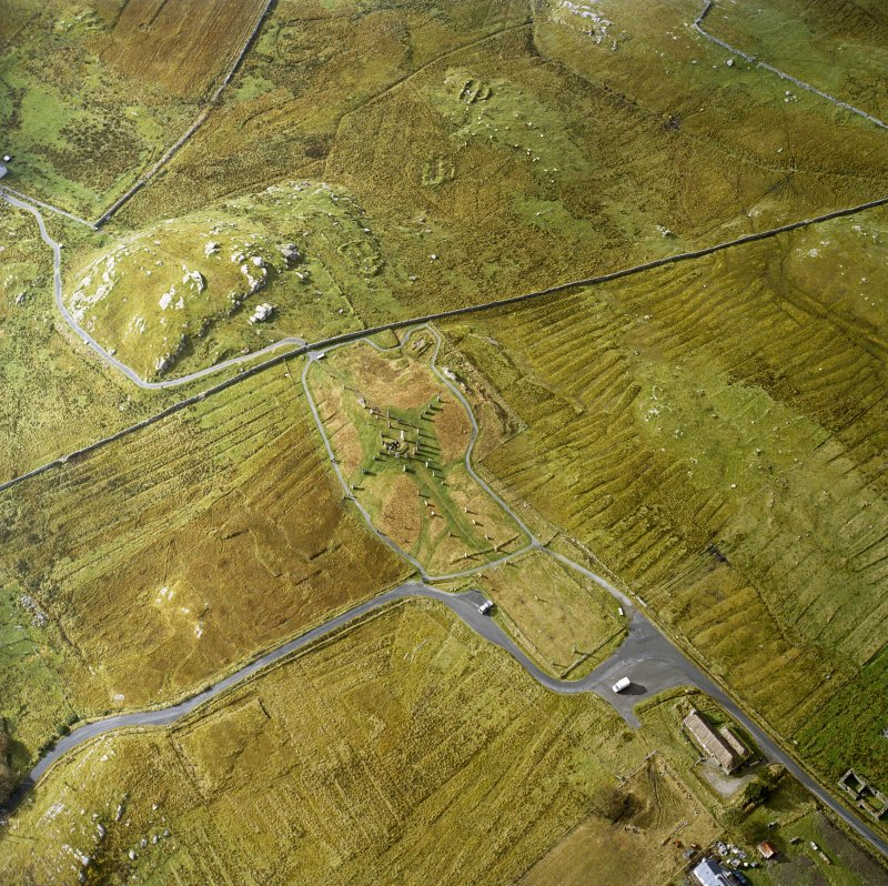 Oblique aerial view centred on the remains of the stone circle, chambered cairn and stone alignments with the township and lazy beds adjacent, taken from the NE.