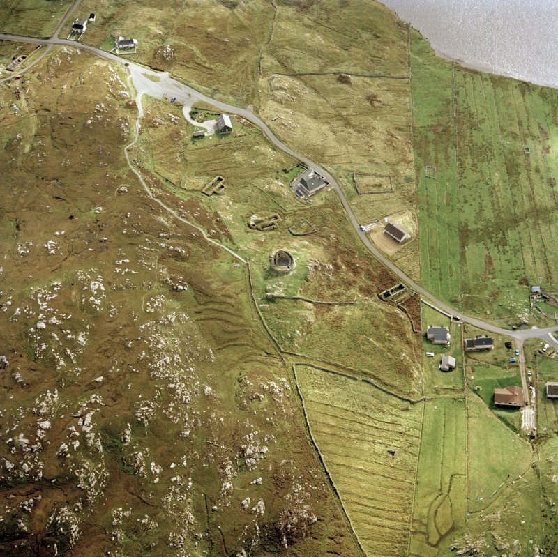 Oblique aerial view centred on the remains of the broch with the remains of the blackhouse and township adjacent, taken from the NNW.