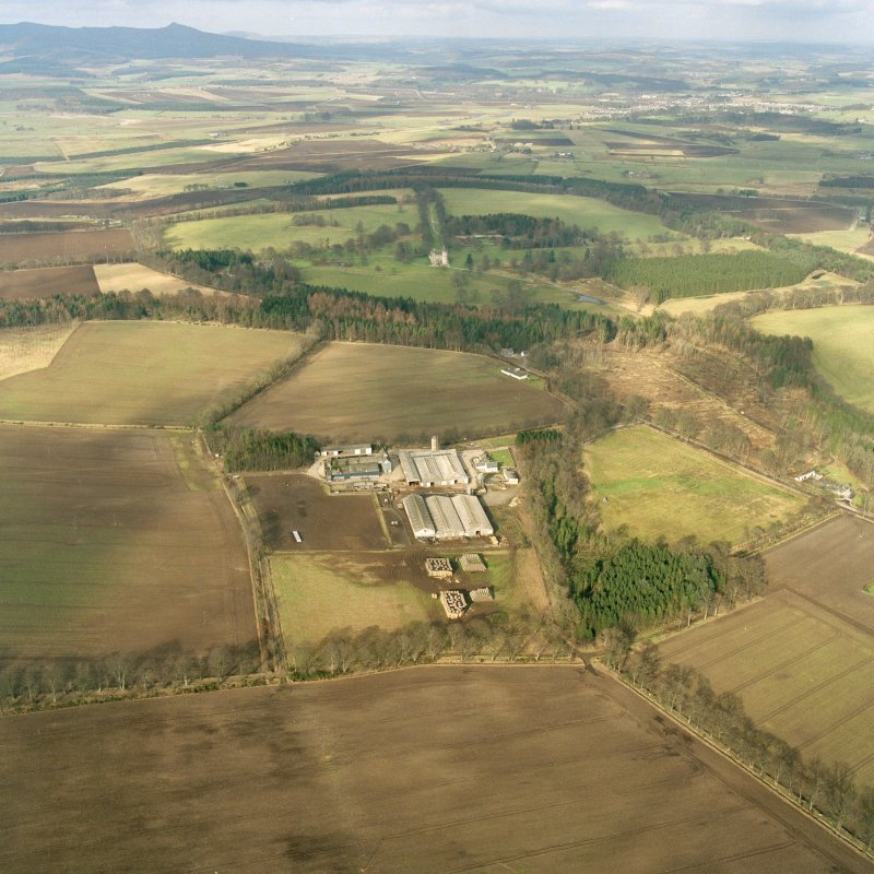 Oblique aerial view of the tower-house and its policies with Bennachie in the background, taken from the S.