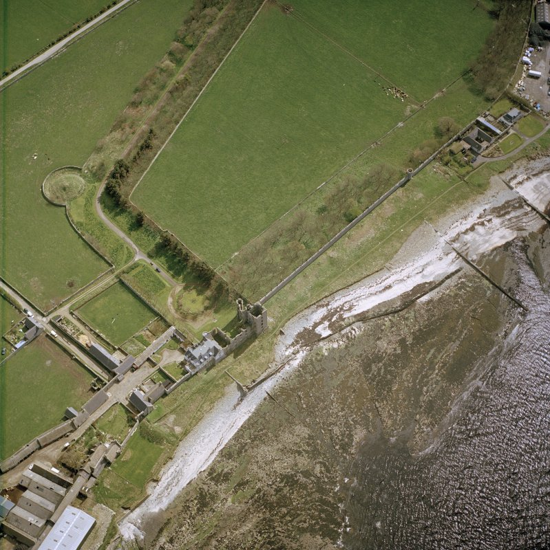 Oblique aerial view centred on the remains of the castle with the farmsteading adjacent, taken from the N.